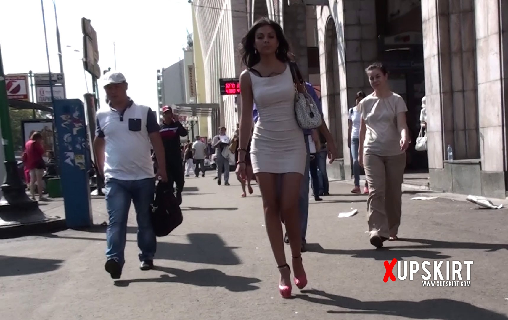 Sexy lady in white dress walks through the street